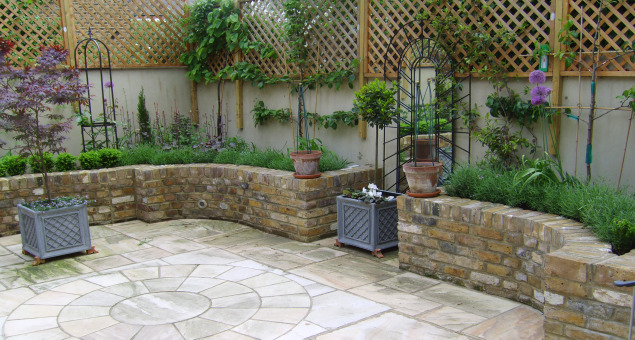 A formal design was implemented to the courtyard with natural sandstone in a colour to complement the yellow London stock bricks of the house for the patio, and reclaimed stocks used to create the raised beds.