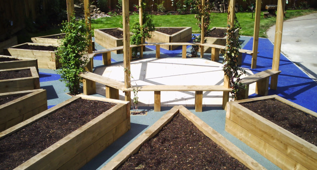 Radiating off from this, new sleeper raised beds were built in which the children can experience the thrill of growing and nurturing their own produce.  Sparkling crushed, recycled glass set in resin surrounds these forming colourful pathways.