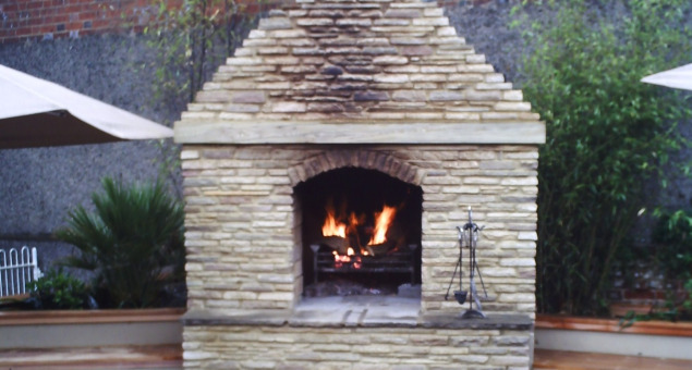 An outdoor fireplace was designed to create both physical warmth and a draw to passers-by, as it could be seen through the archway leading to the road.