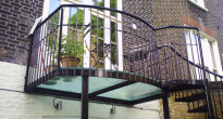 image of a family garden with a glass balcony and spiral staircase to garden
