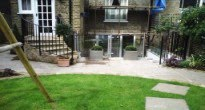 urban garden with glass bifold doors and glass balustrades
