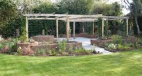 oak arbour on patio surrounded by raised beds with a circular theme