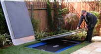 Small garden with hidden trampoline under artificial lawn