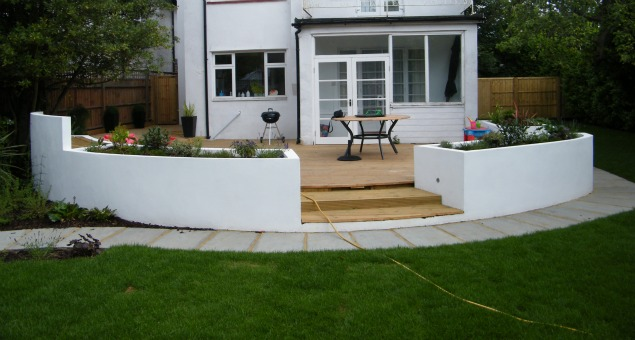 Next to the house we created a spacious, decked seating area surrounded by raised planting beds, rendered and painted white to match the house.