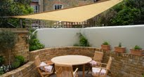 Small garden with shade sail over seating area and raised brick beds