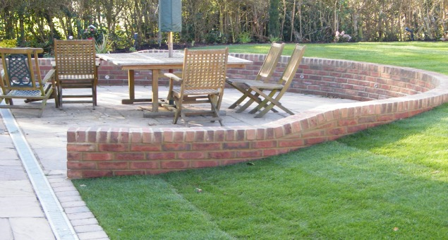 Some of the slope was taken out of the lawns by building a retaining wall around the existing patio, creating a real feeling of intimacy in the dining area