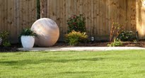Rainbow sandstone sphere in small garden