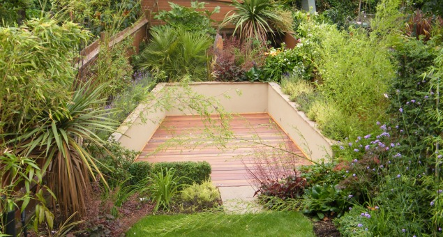 Next to the house a pergola covered balcony affords great views down over the whole garden. A decked area surrounded by raised beds with perfumed planting and a natural stone water feature sits at the end, making use of the awkward angles.