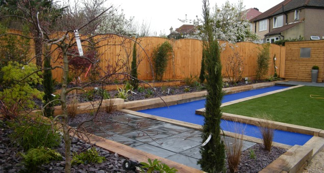 The slate paving used to the side of the house, and in a new additional seating area to the rear of the garden, was matched to the existing patio for continuity, but an exciting contrast was introduced by paving the path with dazzling blue glass.