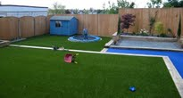 modern garden with astro turf and sunken trampoline leading off a blue glass path