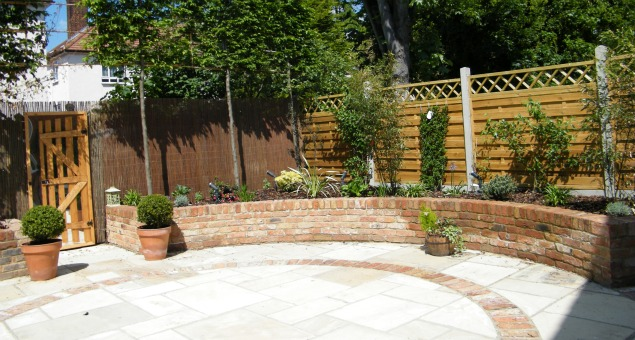 We chose natural sandstone for the paving and used soft red brick for the walling and inset brick details to complement the red brick of the house.