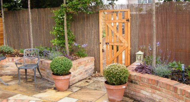 The mirror with half open gate creates the illusion of another beautiful garden beyond.