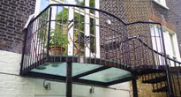 Glass balcony leading to small city garden