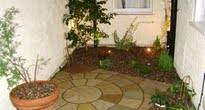 Tiny paved courtyard with lighting