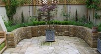Courtyard transformed to natural raised bed and sandstone paving