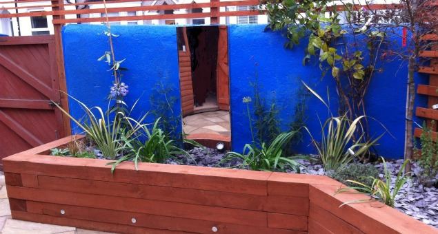 Our clients were fond of their blue back wall, which we kept and we changed the existing trellis on top to give a more contemporary feel.  We included a contemporary, self-contained water feature, using a combination of stainless steel and glass, to add the pleasing dimension of sound and movement.