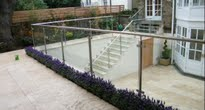 Contemporary travertine patio with glass balustrade
