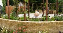 Large garden with modern patio and large sandstone water feature