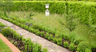 image of formal garden and urn in the continuing meadow grass