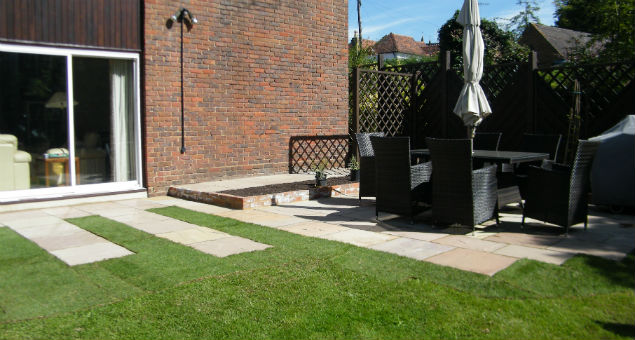 The patio that is to one side of the house in the rear garden