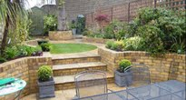 Small garden in Camden with raised lawn and planting beds