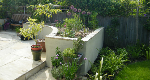 Another view of one of the raised planting beds that edge the patio. The herb pots can be seen in the foreground