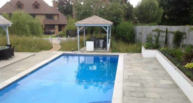 View of the pool, BBQ area and surrounding paving with the house in the background