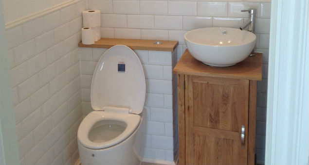 The newly fitted toilet with oak storage unit