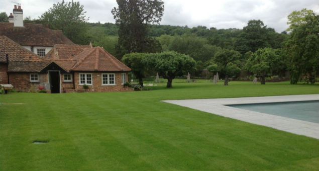The newly laid lawn next to the pool with a view to the out buildings of the house