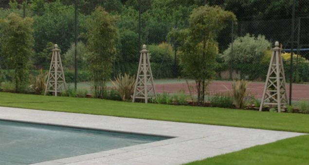 View from the pool across planting beds that reflect the formal beds in the croquet lawn, into the tennis court