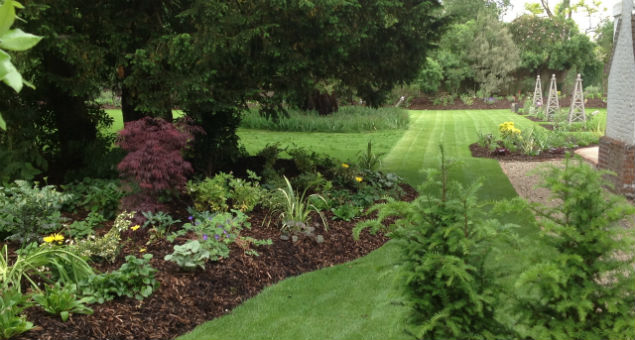As you walk around the side of the house the beds on the side of the croquet lawn come into view