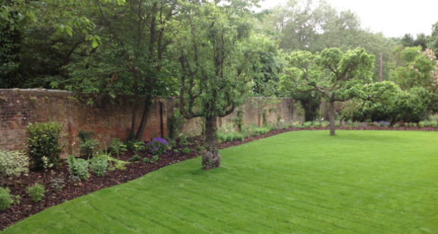 Here the planting beds edge the new lawn and the garden is secluded behind the garden wall