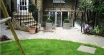 family garden with glass balustrades and bifold doors onto the garden