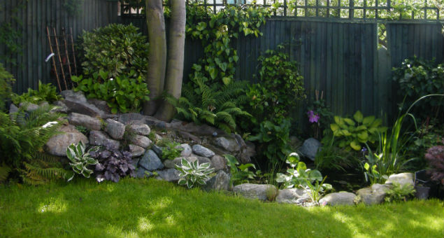 In the top right hand corner of the garden is a pond incorporating a waterfall with a gentle slope edged in boulders