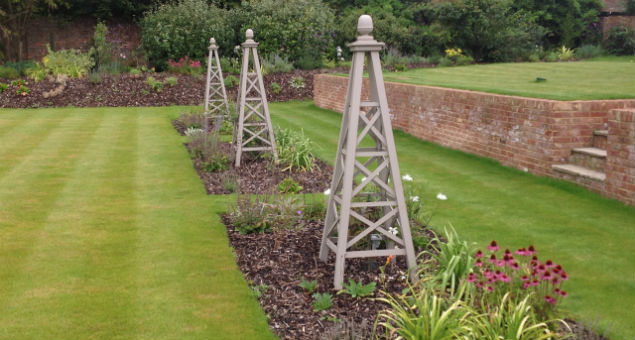 The obelisks and beds along one side of the garden with the retaining walls and step to the upper level