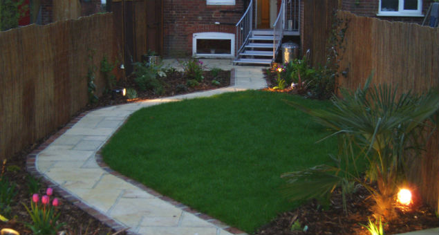The small garden is made to appear wider with a curved path around the lawn