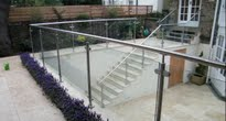 Contemporary garden with travertine paving and glass balustrade