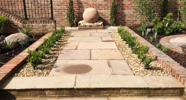 Sandstone path to water feature edged by box hedging plants