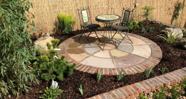 Small seating area on a sandstone circle with brick edging