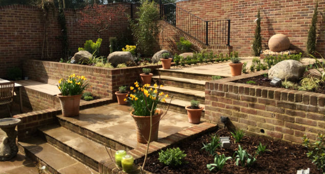 Lavender flanks the steps and flowers in pots soften the area