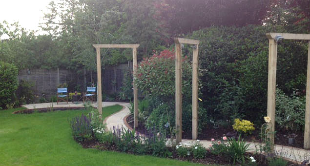 Curved path with planting and arches that mirror the arbour